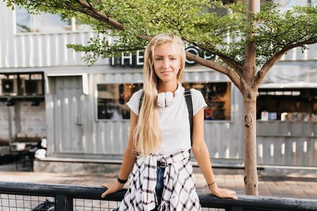 Hermosa mujer en auriculares blancos de pie en el fondo de la calle