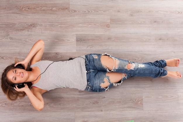 Hermosa mujer con auriculares tirado en el piso