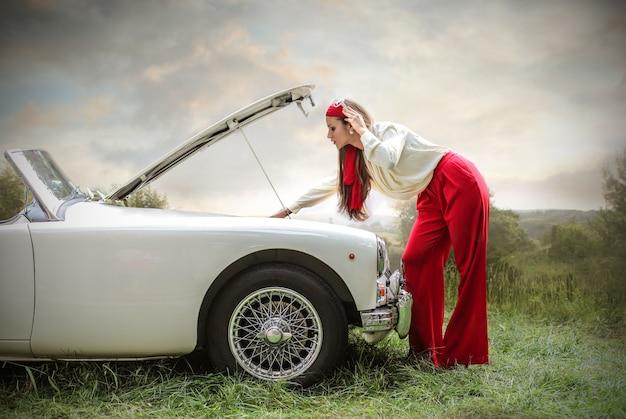 Hermosa mujer en una aventura con un auto deportivo