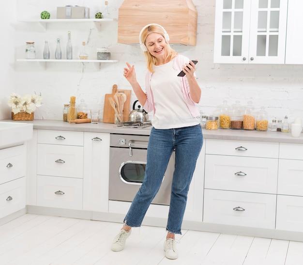 Hermosa mujer bailando con música en la cocina