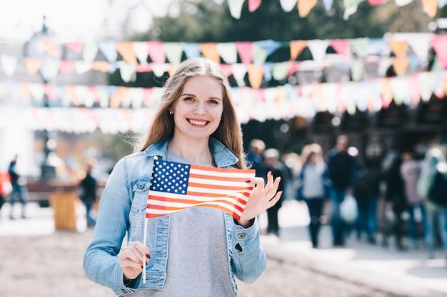 Hermosa mujer con bandera americana en el día de la independencia