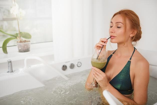 Hermosa mujer en bañera de hidromasaje en el spa center