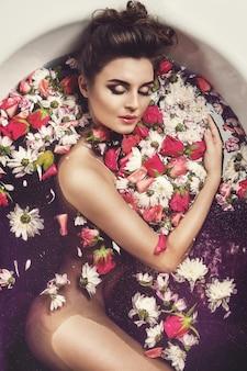 Hermosa mujer en el baño con flores