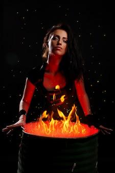 Hermosa mujer y barril de hierro con fuego dentro