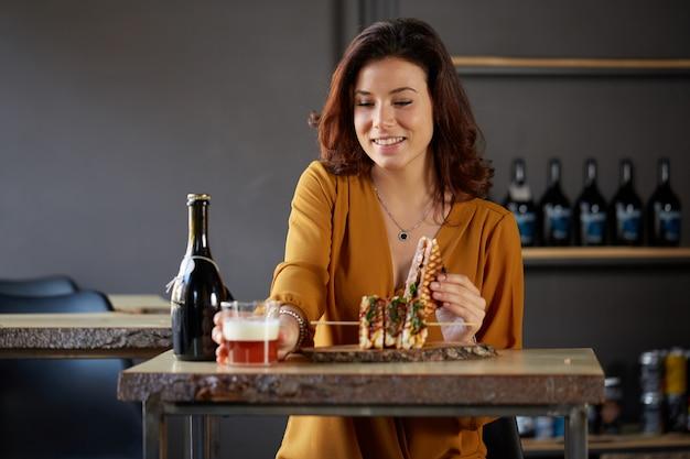 Hermosa mujer bebe una cerveza y come un sándwich club