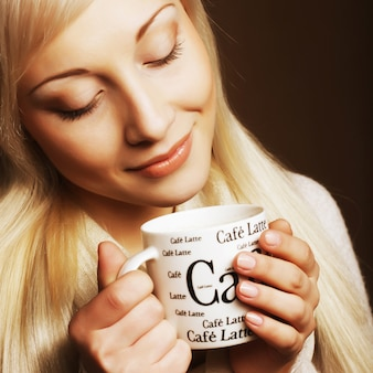 Hermosa mujer bebiendo café cerca