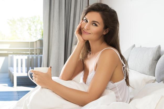 Hermosa mujer bebiendo café o té en el dormitorio