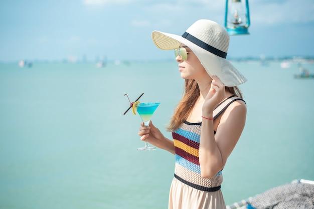 Hermosa mujer está bebiendo hielo bebida de verano en la playa, concepto de verano