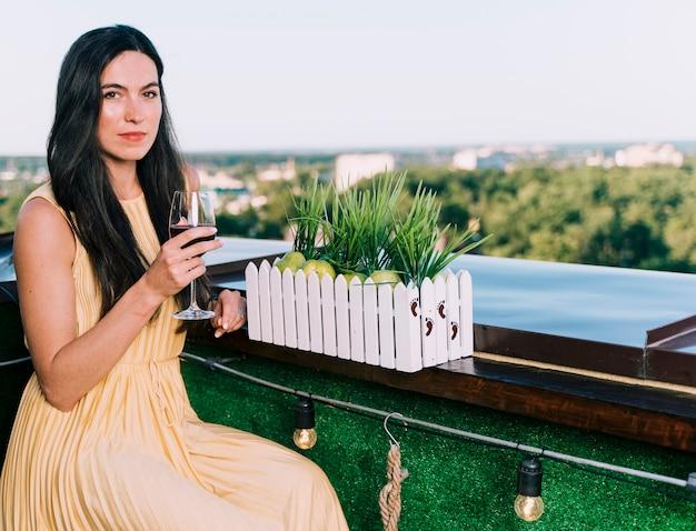 Hermosa mujer bebiendo vino en la azotea
