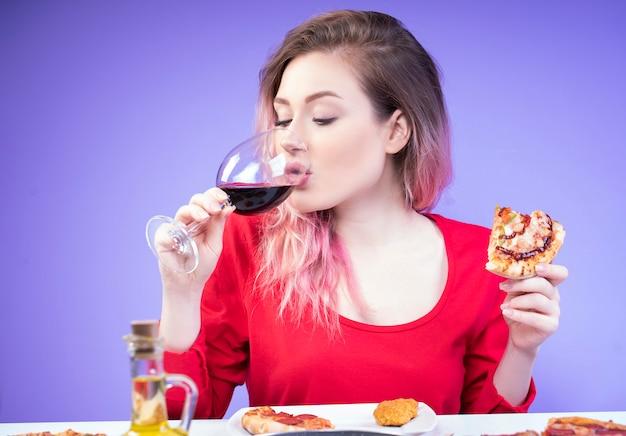 Hermosa mujer bebiendo vino y sosteniendo una rebanada de pizza en la mano