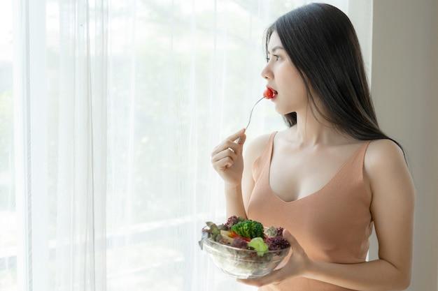Hermosa mujer bella asiática chica linda sensación feliz comiendo dieta comida fresca ensalada para buena salud en la mañana