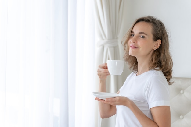 Hermosa mujer de belleza linda chica se siente feliz tomando café en la mañana