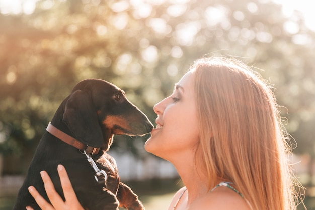 Hermosa mujer besando a su lindo perro