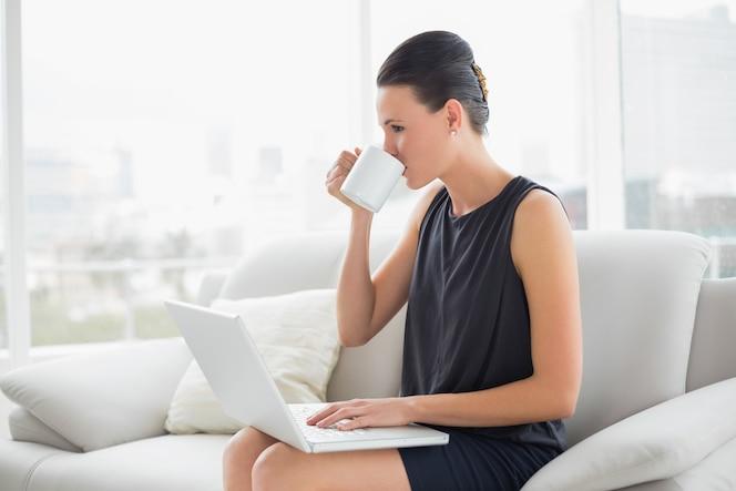 Hermosa mujer bien vestida con ordenador portátil mientras bebe café en el sofá
