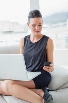 Hermosa mujer bien vestida con ordenador portátil y teléfono móvil en el sofá