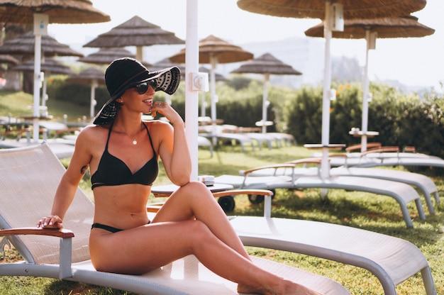 Hermosa mujer en bikini acostado en la cama de la piscina