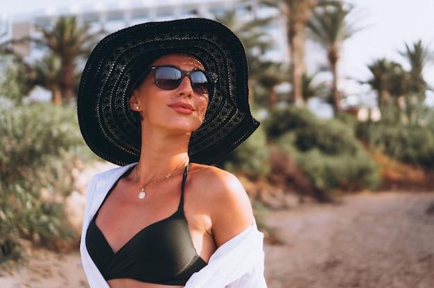 Hermosa mujer en bikini y camisa por palmas