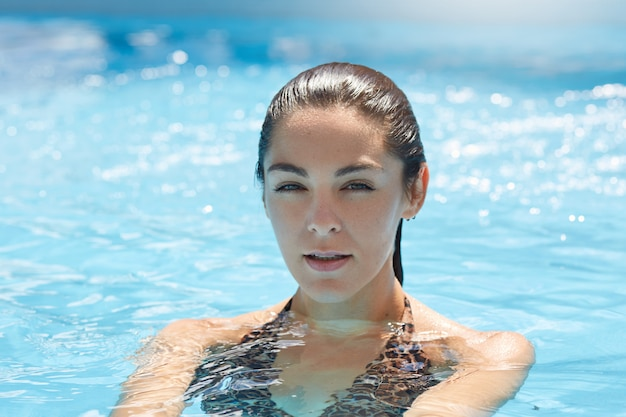 Hermosa mujer en bikini elegante, relajarse en la piscina