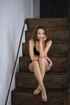 Hermosa mujer en bikini negro sentada en las escaleras de madera en casa
