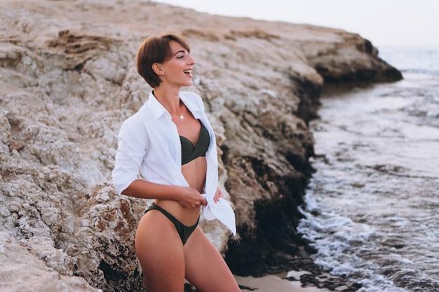 Hermosa mujer en bikini posando junto al océano