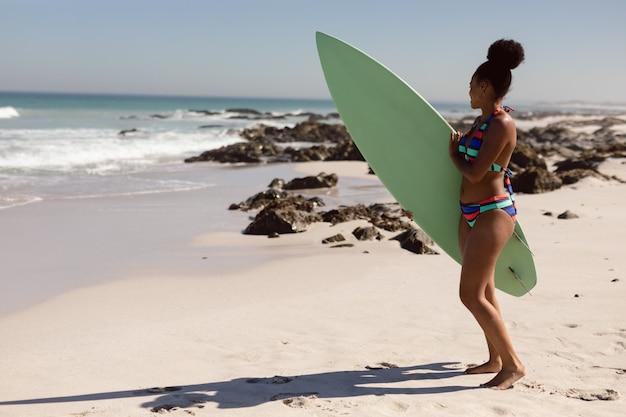 Hermosa mujer en bikini con tabla de surf mirando a otro lado en la playa bajo el sol