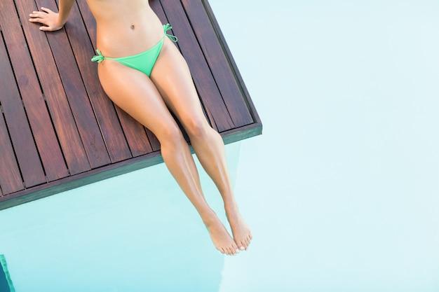Hermosa mujer en bikini verde relajante en la terraza de madera junto a la piscina