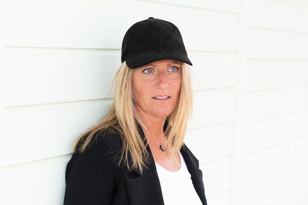 Hermosa mujer blanca con ojos azules en una elegante chaqueta y gorra.