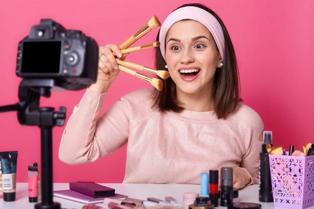 Hermosa mujer blogger estilista sostiene en la mano diferentes cepillos cosméticos, tiene feliz expresión facial, se encuentra con la boca abierta