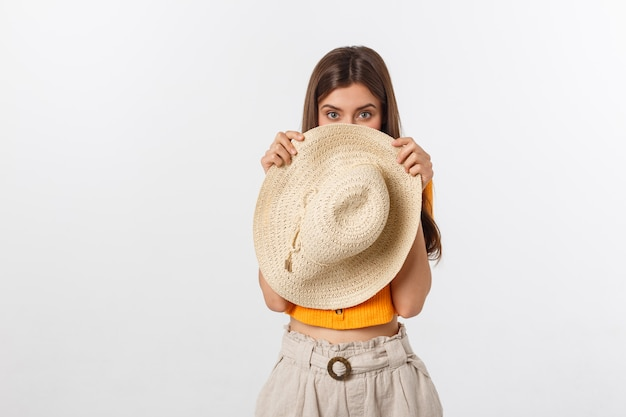 Hermosa mujer con blusa naranja escondiéndose detrás de su sombrero