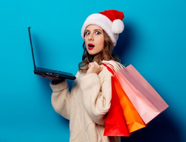 Hermosa mujer con bolsas de compras y computadora portátil en la pared azul