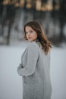 Hermosa mujer en un bosque nevado de invierno
