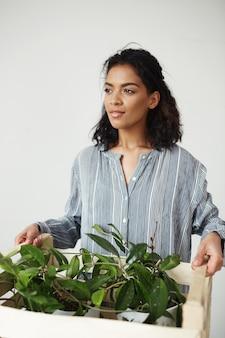 Hermosa mujer botánico sonriente sosteniendo caja con plantas
