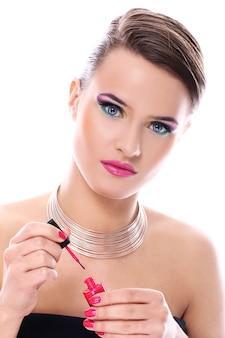 Hermosa mujer con botella de esmalte de uñas rosa