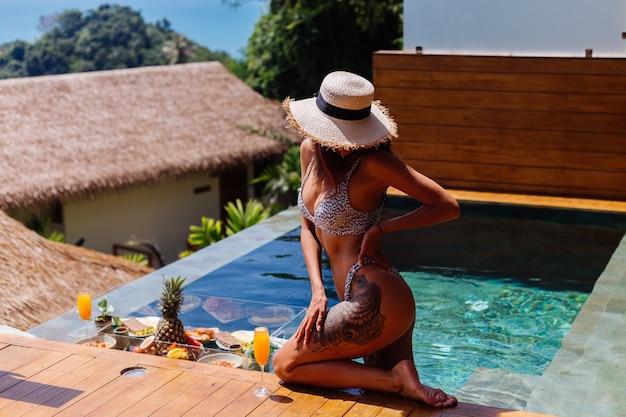Hermosa mujer bronceada caucásica en bikini y sombrero de paja con desayuno flotante en la increíble villa de lujo de estilo bali en un día soleado junto a la piscina, fondo tropical.