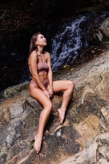 Hermosa mujer bronceada con piel bronceada en bikini sentada sobre una roca por cascada