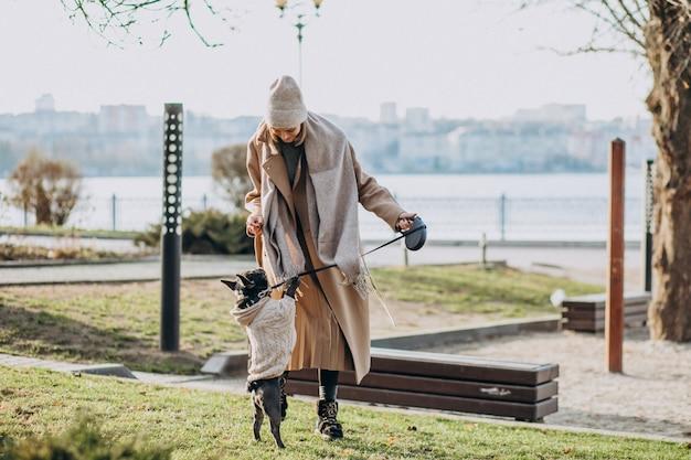 Hermosa mujer con bulldog francés caminando en el parque