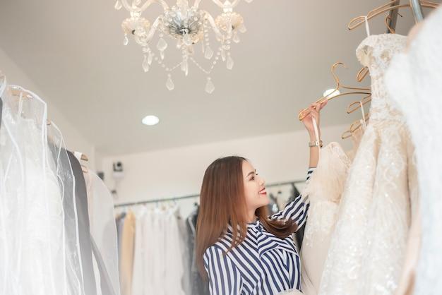 Hermosa mujer busca vestido de novia en la tienda de la boda