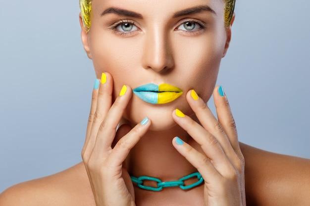 Hermosa mujer con cabello amarillo y coloridas uñas y labios