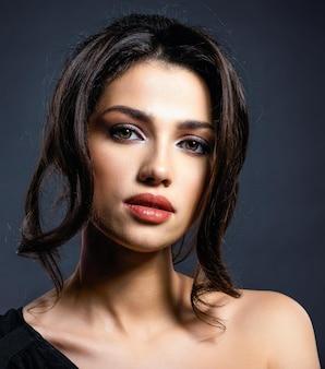Hermosa mujer con cabello castaño. modelo atractivo de ojos marrones. modelo de moda con un maquillaje ahumado. closeup retrato de una mujer bonita. peinado creativo.