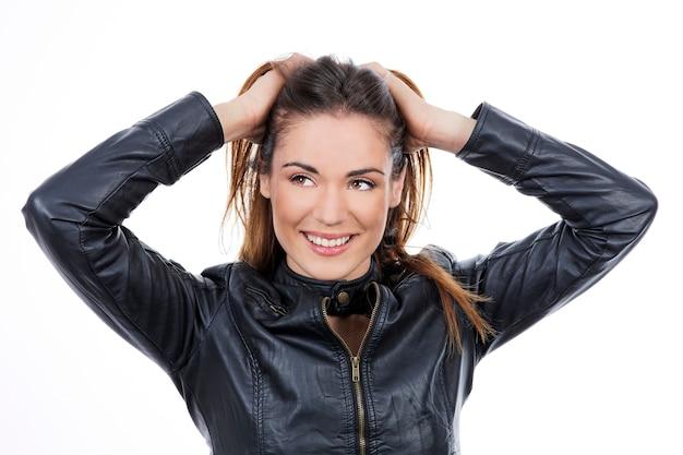 Hermosa mujer de cabello largo castaño con la mano en el cabello