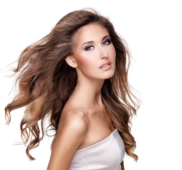 Hermosa mujer con cabello largo castaño en movimiento y maquillaje. aislado en blanco