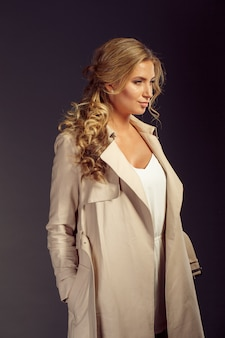 Hermosa mujer con cabello largo y rubio en abrigo de piel beige