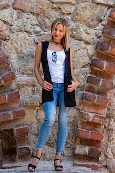 Una hermosa mujer con cabello largo y rubio, una blusa blanca y jeans azules junto al muro de piedra del casco antiguo