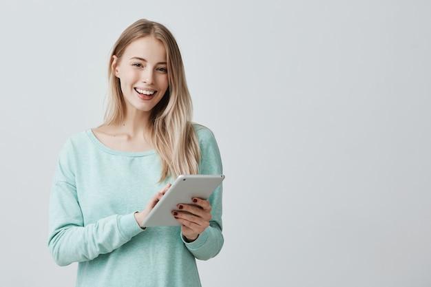 Hermosa mujer con cabello largo y rubio con tableta para educación o trabajo en la compilación de gráficos de negocios.