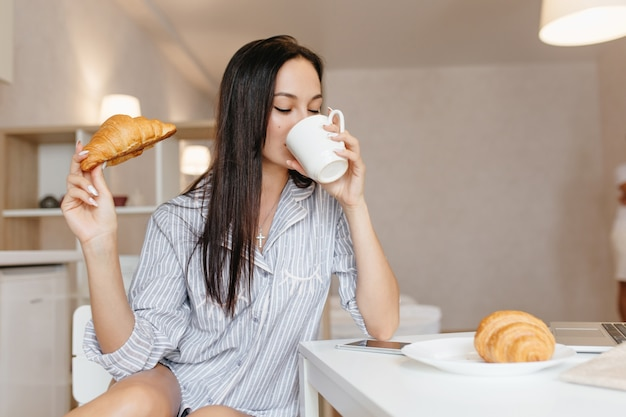 Hermosa mujer con cabello negro brillante tomando café durante el desayuno