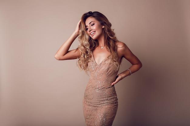 Hermosa mujer con cabello ondulado rubio con elegante vestido beige