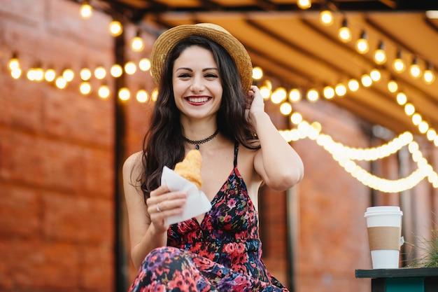 Hermosa mujer con cabello oscuro, apariencia atractiva, con sombrero, vestido y collar