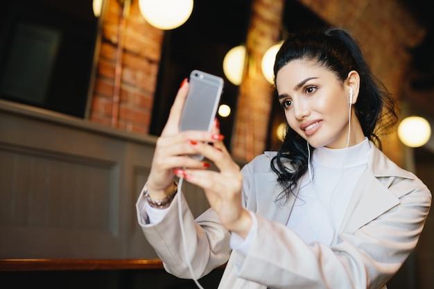 Hermosa mujer con cabello oscuro atado en cola de caballo haciendo selfie mientras está sentado en la cafetería con su teléfono inteligente