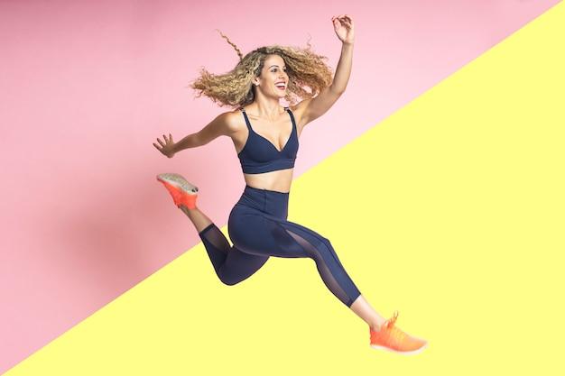 Hermosa mujer con cabello rizado rubio con bonita sonrisa es feliz sonriendo y vestida con ropa deportiva está saltando