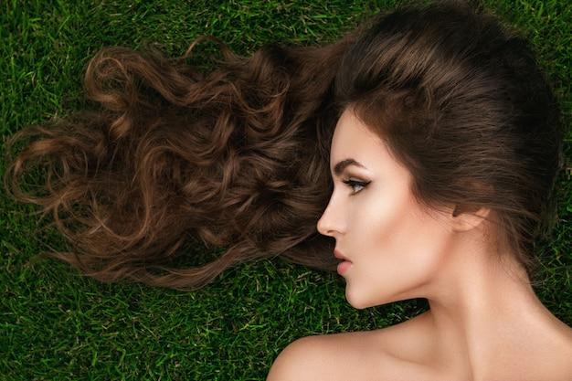 Hermosa mujer con un cabello rizado sano está tumbado en la hierba